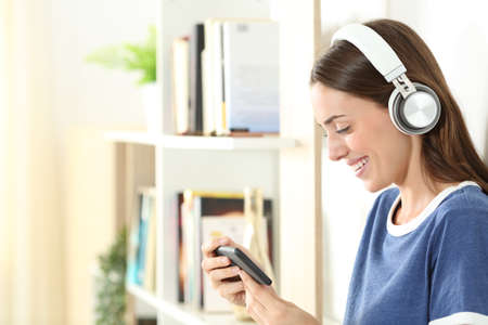 Profile of a happy teen wearing wireless headphones watching media on smart phone at home