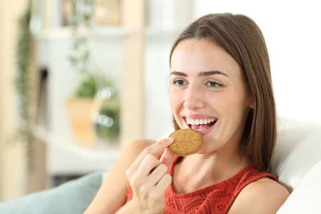 Happy woman is eating cereal cookie sitting on a couch in the living room at home Stockfoto