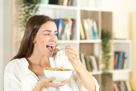 Happy girl opening mouth eating cereal for breakfast at home