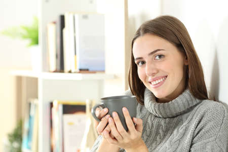 Happy woman wearing sweater looks at you holding coffee cup in winter standing at home Standard-Bild