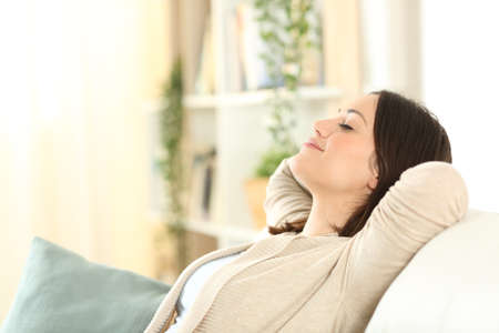 Woman resting and relaxing sitting on a comfortable couch in the living room at home