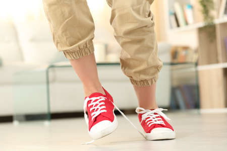Front view of a woman legs stumbling with shoelaces walking at home
