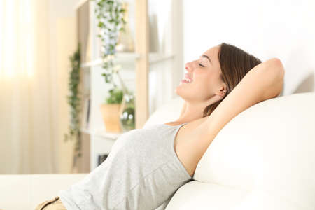 Side view portrait of a happy woman with waxed armpit relaxing sitting on a sofa in the living room at home Stock fotó