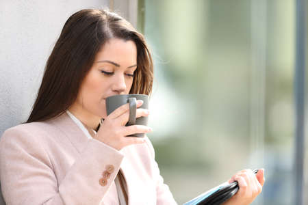 Businesswoman drinking coffee and reading inform standing in the street 免版税图像