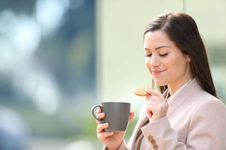Entrepreneur eating cookie and drinking coffee at breakfast standing on the street