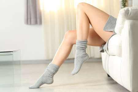 Side view portrait of a beauty woman legs with socks posing in winter sitting on a couch at home