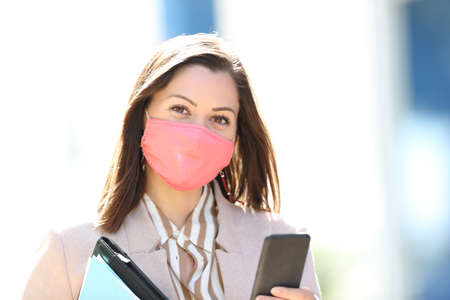 Happy entrepreneur wearing mask avoiding coronavirus contagion and holding smart phone posing looking at you in the street