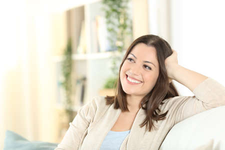 Happy woman thinking looking at side sitting on a couch in the living room at home