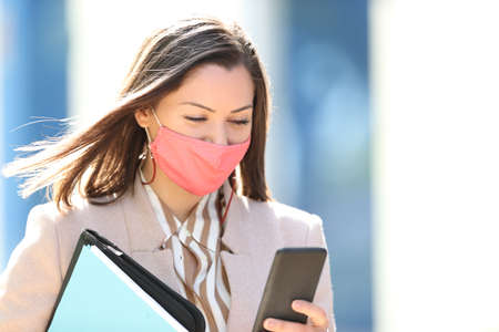 Businesswoman wearing mask avoiding coronavirus reading smart phone content walking in the street