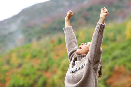 Middle age excited woman raising arms celebrating in the mountain