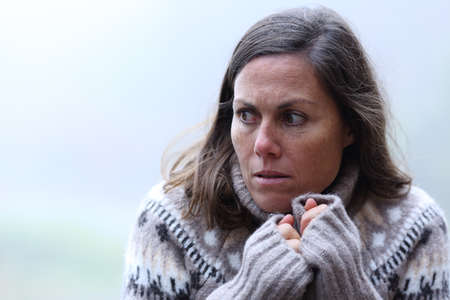Scared middle aged woman standing in a forest a foggy day of winter