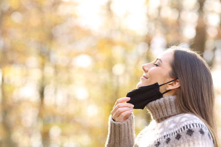 Side view portrait of a satisfied woman relieving taking off protective mask to breath fresh air in fall season in a park Foto de archivo