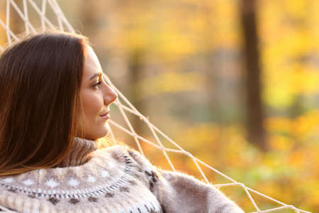 Side view portrait of a relaxed woman contemplating views on hammock in a forest in autumn at sunset