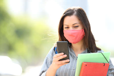 Student with mask avoiding coronavirus or pollution using smart phone walking in the street Banque d'images