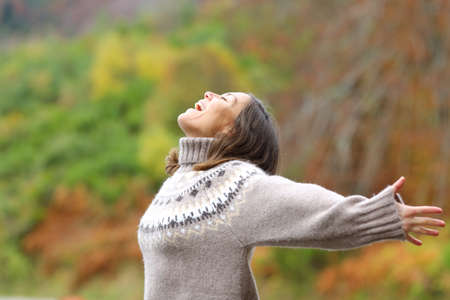Profile of a middle age excited woman celebrating outstretching arms in the mountain in autumn season