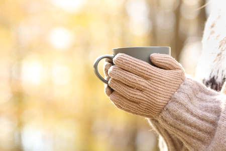 Close up of woman hands with gloves holding coffee mug in autumn in a park