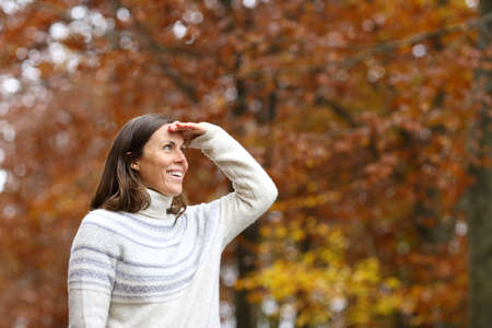 Happy adult woman searching with hand on forehead in a forest in autumn