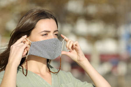 Woman walking putting mask due covid in the street