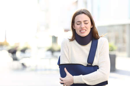 Front view portrait of a stressed woman suffering with broken arm on a sling walking in the street