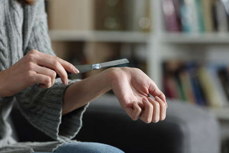 Close up of a woman hands trying to suicide cutting her veins with a cutter on a couch at home