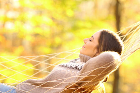 Side view portrait of woman resting lying on hammock in autumnal forest