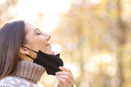Side view portrait of a satisfied woman taking off mask breathing fresh air in a park