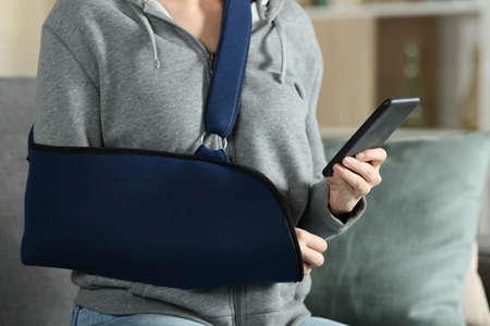Close up of woman hands with broken arm wearing sling using smart phone at home