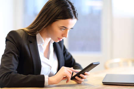 Business woman checking mobile phone working in a table at office
