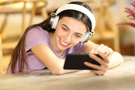 Happy female watching videos on smart phone wearing headphones at home Stok Fotoğraf