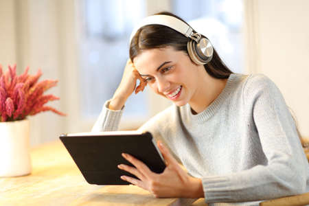 Happy woman wiearing headphones watching tablet content at home