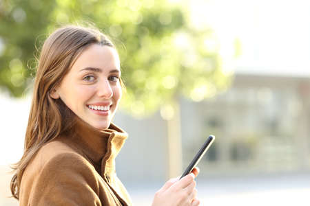 Happy woman holding mobile phone looks at you in winter in the street