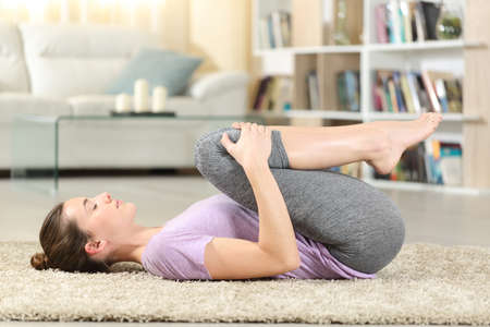 Profile of a concentrated woman doing yoga exercise on the floor at home