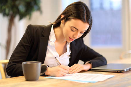 Happy businesswoman signing paper form working at office