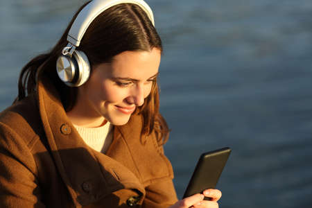 Happy female listening to music with smart phone and headphones on the beach in winter Stok Fotoğraf