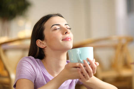 Happy woman smelling coffee breathing fresh air at home