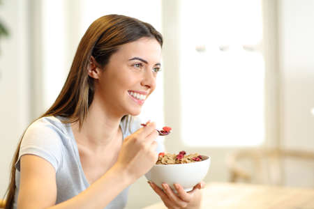 Happy woman eating cereals from bowl for breakfast in the living room at home