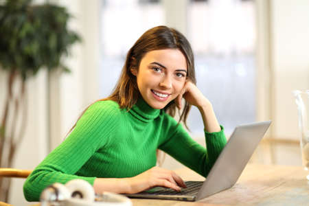 Happy woman with laptop looks at camera in the living room at home