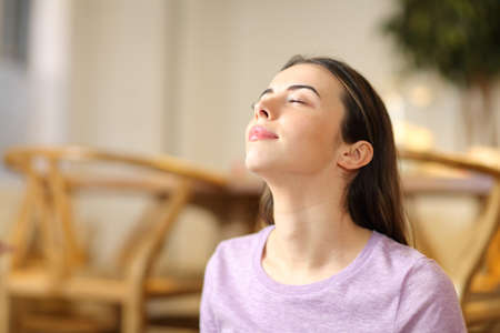 Happy woman breathing fresh air relaxing alone at home