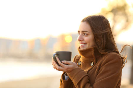 Happy woman drinking coffee in winter looking away on the beach at sunset