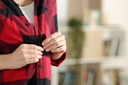 Close up of a teenager hand undressing fastening button of red shirt standing at home Stok Fotoğraf