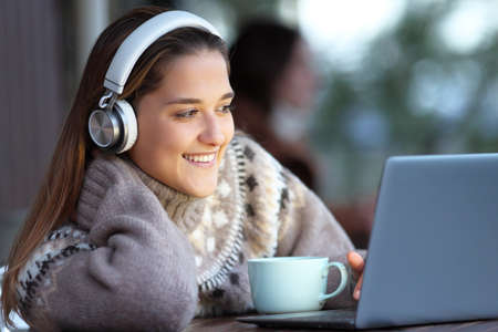 Happy woman wearing headphones watching and listening media on laptop sitting in a bar Stok Fotoğraf