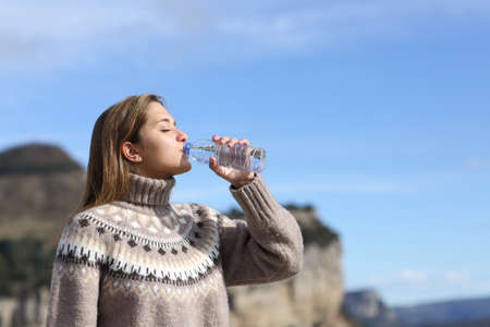 Side view portrait of a woman drinking water from plastic bottle in winter in the mountain Stok Fotoğraf