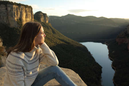 Pensive woman contemplating views in the top of a cliff in the mountain at sunset in winter