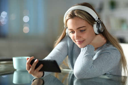 Teen watching videos on smart phone wearing headphones in the night in the living room at home Stok Fotoğraf