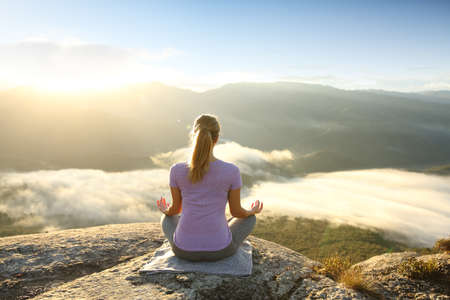 Back view of a woman in the top of a cliff meditating doing yoga
