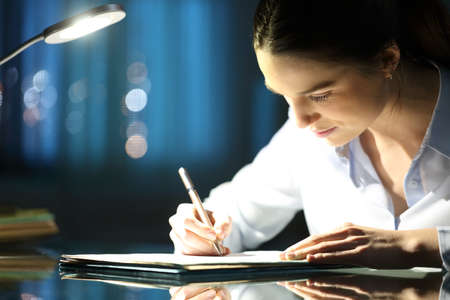 Woman filling paper form late hours in the night at office