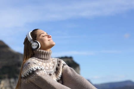 Happy woman relaxing listening to music with wireless headphones in the mountain in winter