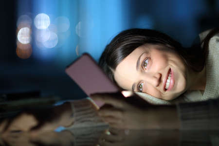 Happy woman late hours in the night checking smart phone content at home Stok Fotoğraf