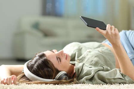 Happy woman listening to music with smart phone and headphones lying on a carpet at home