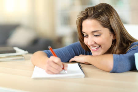 Happy woman taking notes on notebook in a table at home